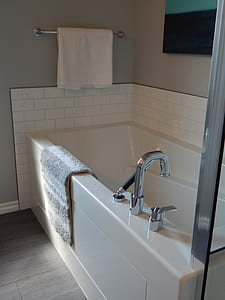 white ceramic bathtub with white towel hanged on silver towel bar