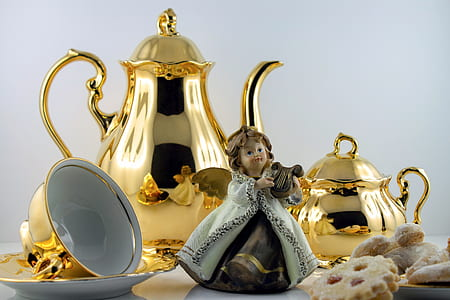 angel playing wind instrument figurine beside gold-colored teapots and teacup