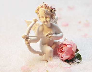 selective focus photography of white marble cupid figurine with pink rose