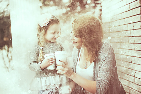smiling woman and child holding disposable cups