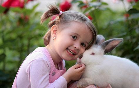 toddler girl beside white rabbit during daytime