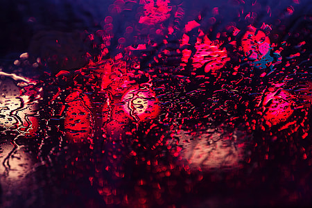 Abstract shot of rain and lights through glass texture window