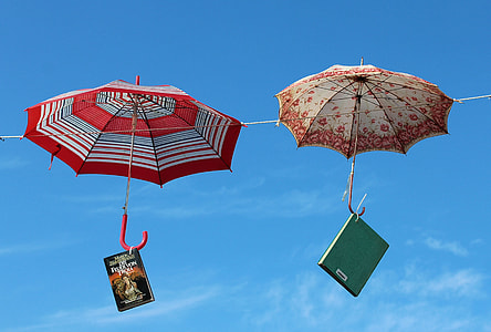 two umbrellas on hanged on wire under blue calm sky