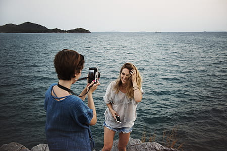 short haired woman in blue top taking photo of another woman in white top standing beside body of water