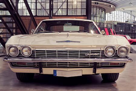 classic beige Chevrolet car parked inside building