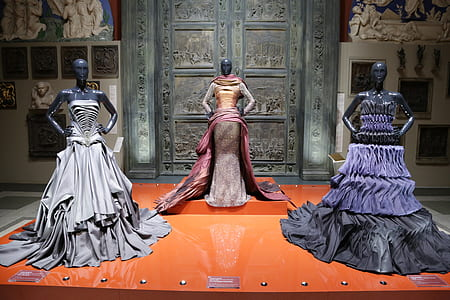 three mannequins wearing dress beside close door