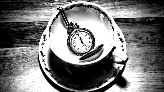 grayscale photo of pocket watch on teacup with saucer