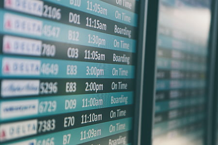 selective focus photography of plane flight schedule board