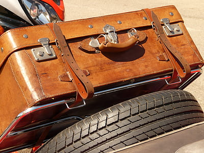 brown leather suitcase beside black auto tire