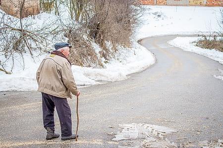 man in brown jacket in walking gesture during winter season
