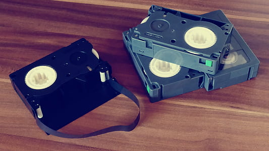 Betamax Tapes on Top of Brown Wooden Surface