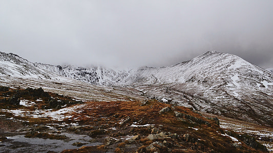 photo of snow covered mountain under grey sky