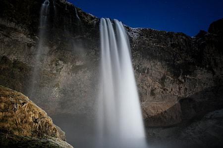 waterfalls inder indigo sky at nightime