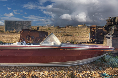 An old abandoned speed boat sits on the shingle beach at Dungeness, Kent, England