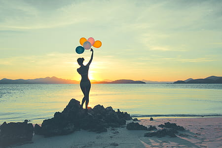 silhouette photo of woman holding assorted-color balloons standing on rock formation during sunset