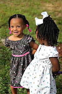 tilt shift lens photography of two black haired girl wearing white and black dresses