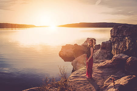 woman standing on brown edge of rock