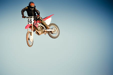man riding in red dirt bike