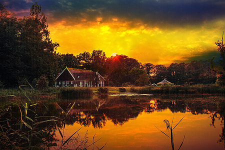 sunset over brown wooden cabin near lake