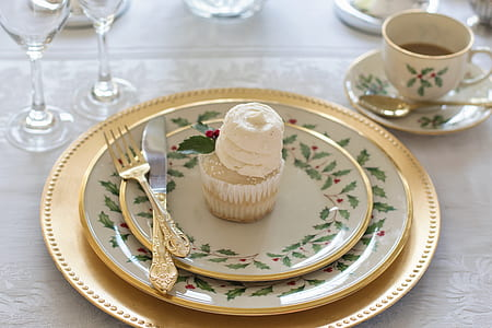 cupcake with three round ceramic plates and dinner knife and fork