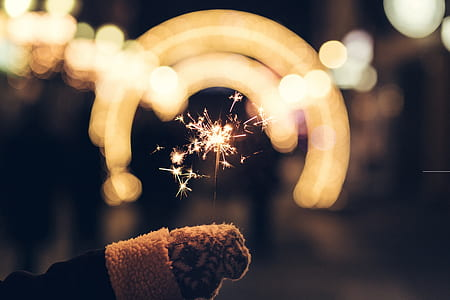 bokeh photography of person holding sparkler