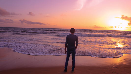man standing on seashore during golden hour