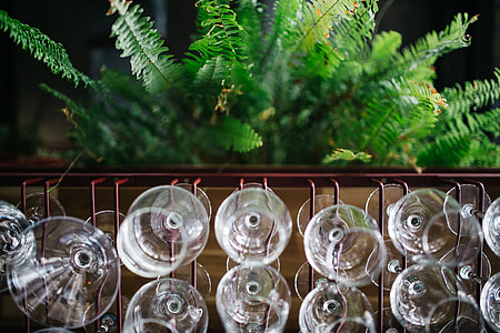 A big bunch of wine glasses hanging from a holder