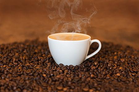 photo of hot coffee on coffee seeds