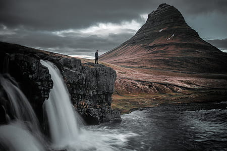 person standing atop waterfall near brown hill