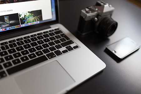gray MacBook beside of DSLR camera
