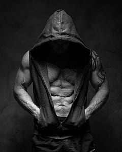 man wearing hooded vest on grayscale photo