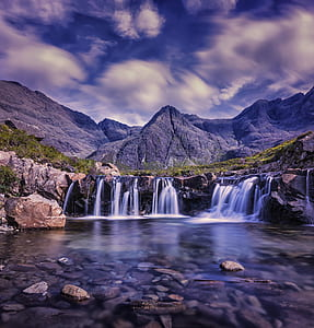 photography of waterfalls near mountains