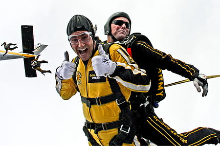 two men wearing black and yellow safety suits