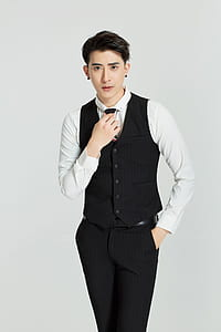 man wearing black button-up vest, white dress shirt and black dress pants outfit