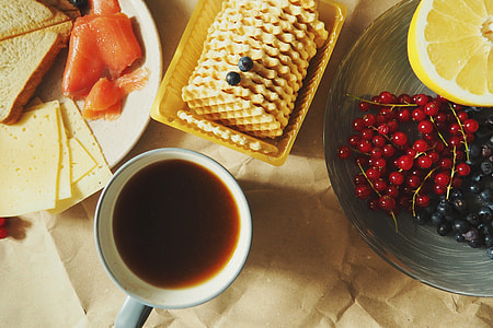 Overhead shot of coffee, biscuits, cheese and fruits