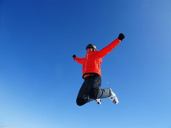 Man in Orange Zip Jacket and Black Pants Jumping Under Blue Sunny Sky