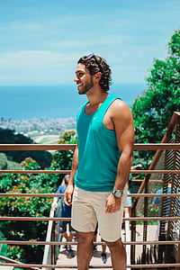 person in blue tank top standing near railings