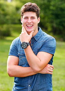 man smiling wearing denim button-up shirt