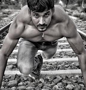 man wearing jeans standing on train tracks