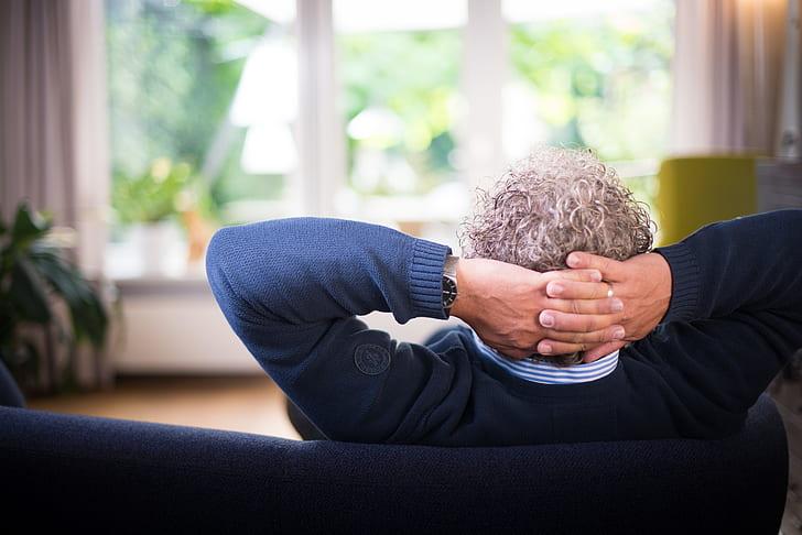 man in blue sweater sitting on blue sofa