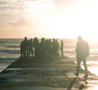 silhouette photo of group of people standing on beach dock