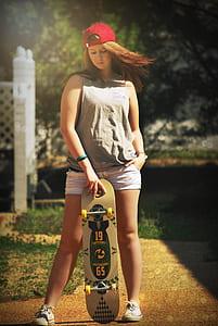 woman in gray tank top holding skateboard