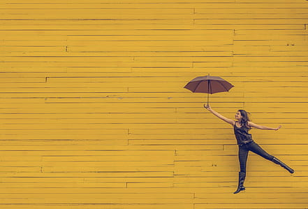 woman holding umbrella jumping on yellow background