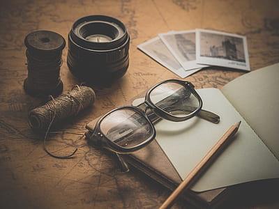 black framed wayfarer eyeglasses beside black camera lens