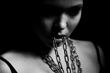 grayscale photography of woman eating chain