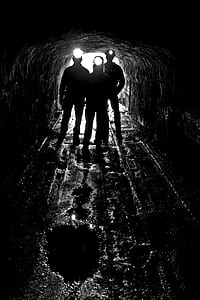 silhouette of three person on cave with headlamp