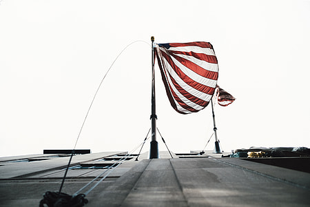 white and red striped flag with pole at daytime