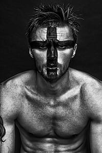 man with painted face grayscale photo