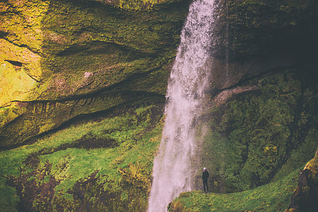 man standing on mountain with falls