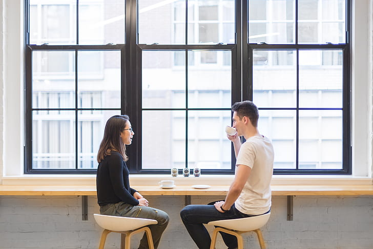 man wearing white t-shirt holding teacup on right hand talking to woman wearing black shirt while sitting on chairs